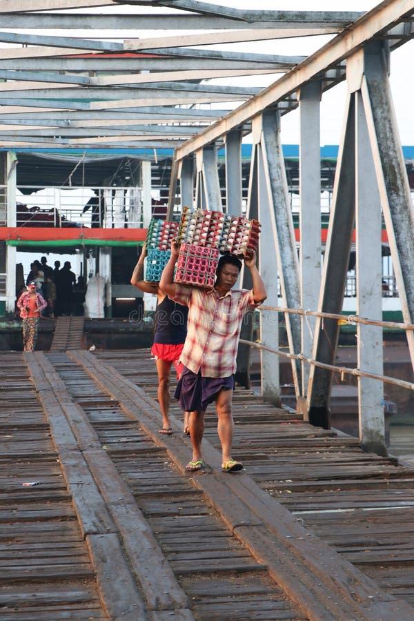 2 лейбориста Myanmese носят утку яйца в клети debark от корабля и прогулки за мостом гавани на реке Янгона стоковая фотография rf