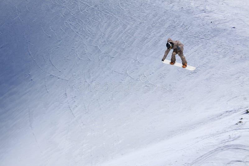 Летание Snowboarder на предпосылке снежного наклона Весьма спорт зимы, сноубординг стоковое фото
