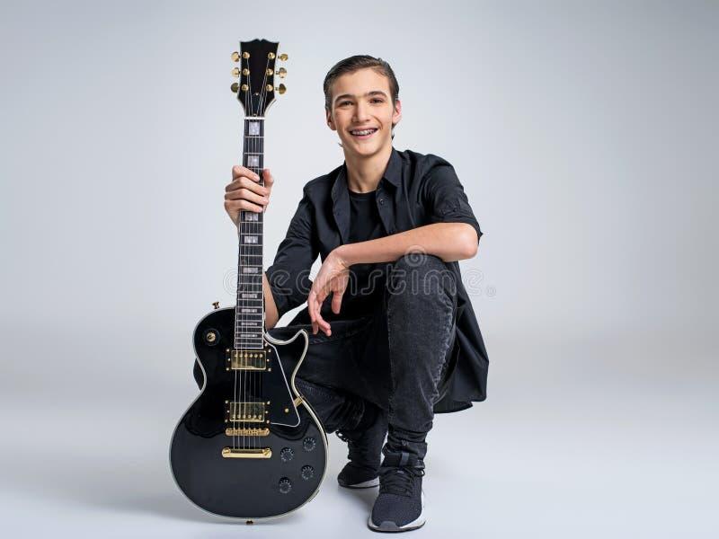 15 лет старого гитариста с черной электрической гитарой стоковое изображение rf