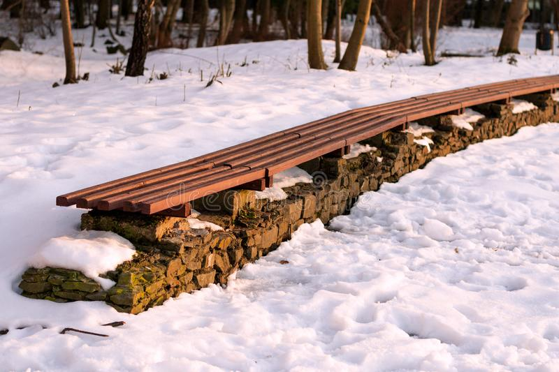 Линия пустой скамейки в парке зимы в солнечном дне Концепция ослабляет, комфорт, парк украшая, морозная погода, красивый ландшафт стоковая фотография