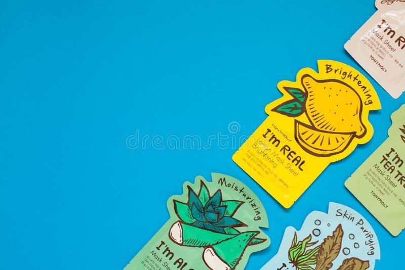 Лист хлопка Tony Moly маскирует положение квартиры на голубой предпосылке Корейский взгляд сверху косметик стоковые изображения