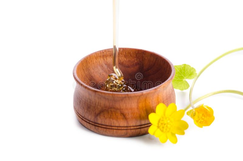 Лить мед в деревянном шаре с желтыми цветками стоковое изображение rf