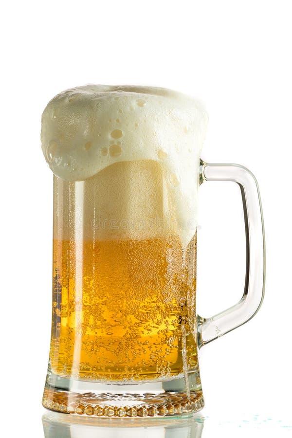 Лить светлое пиво в кружке пива, оно поворачивает вне пену и брызги стоковое изображение