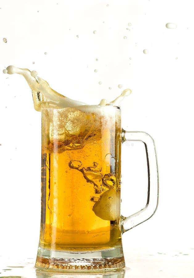 Лить светлое пиво в кружке пива, оно поворачивает вне пену и брызги стоковая фотография