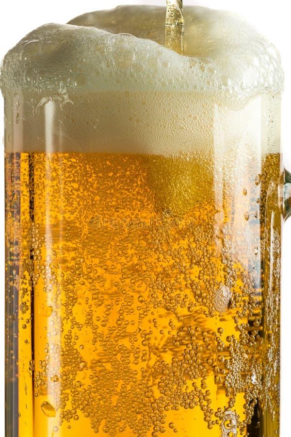 Лить светлое пиво в кружке пива, оно поворачивает вне пену и брызги стоковые фотографии rf