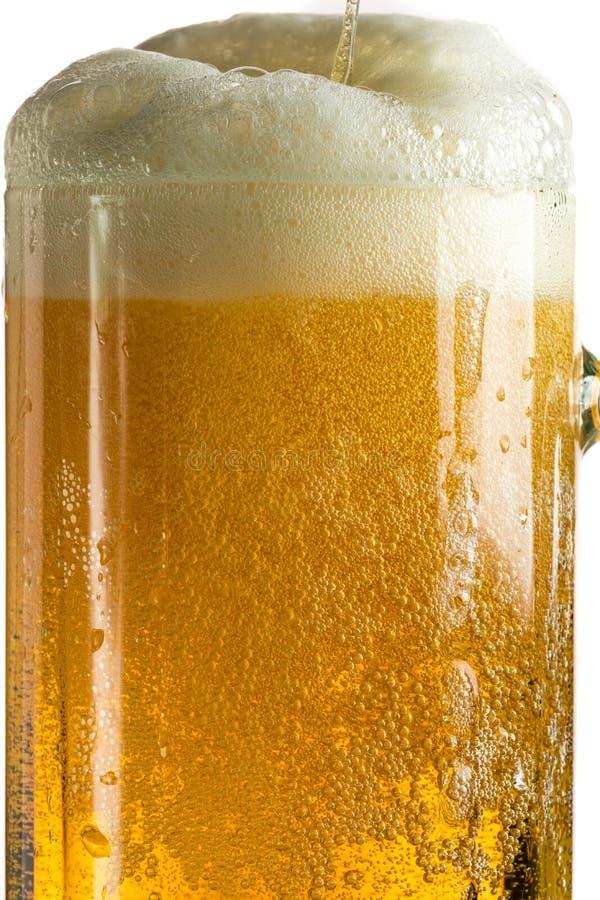 Лить светлое пиво в кружке пива, оно поворачивает вне пену и брызги стоковое фото