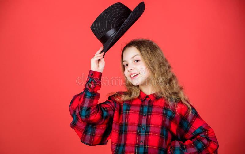Любить ее новый стиль Фотомодель наклоняя ее шляпу в салютовать Маленькая девочка с милой стороной и длинной прической мало стоковое изображение