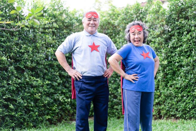 Любя пары имеют потеху в парке Счастливые азиатские старшие пары играя outdoors Пожилые супруг и жена в костюмах супергероя стоковое изображение rf