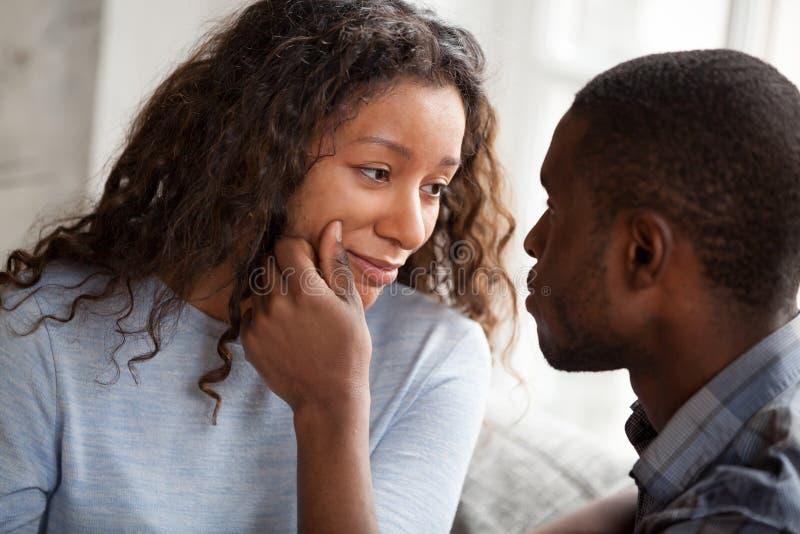 Любя чернокожий человек веселя грустную молодую девушку стоковое фото