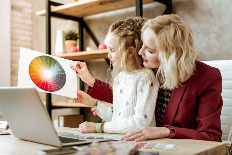 Любопытный воодушевленный длинн-с волосами ребенк наблюдающ бумагой с напечатанной цветовой палитрой стоковые фото