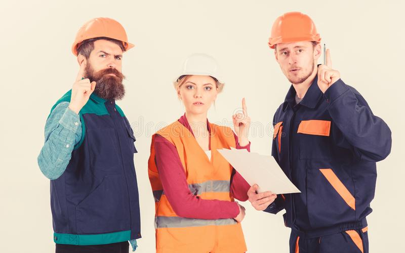 Люди в защитных шлемах, форме и женщине Построитель и инженер стоковое изображение