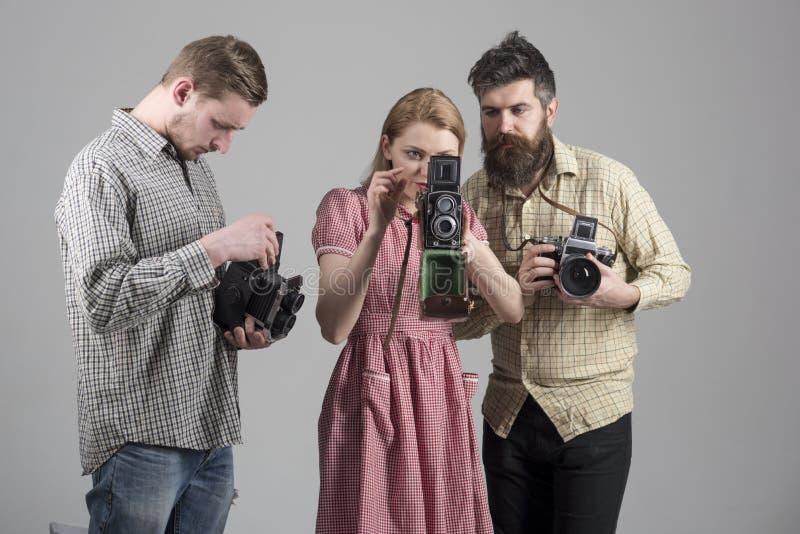Люди в checkered одеждах, ретро стиле Компания занятых фотографов с старыми камерами, киносъемка, деятельность Люди и женщина стоковые фото