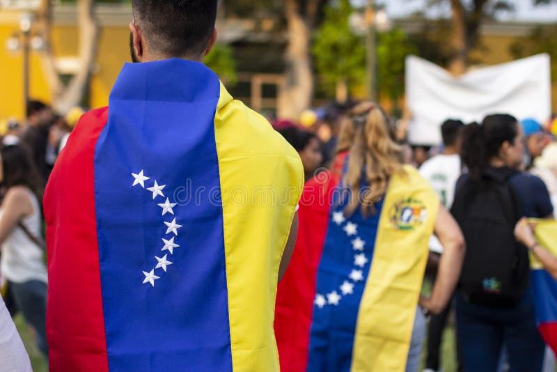 Люди в оболочке в венесуэльских флагах на протесте стоковое фото rf