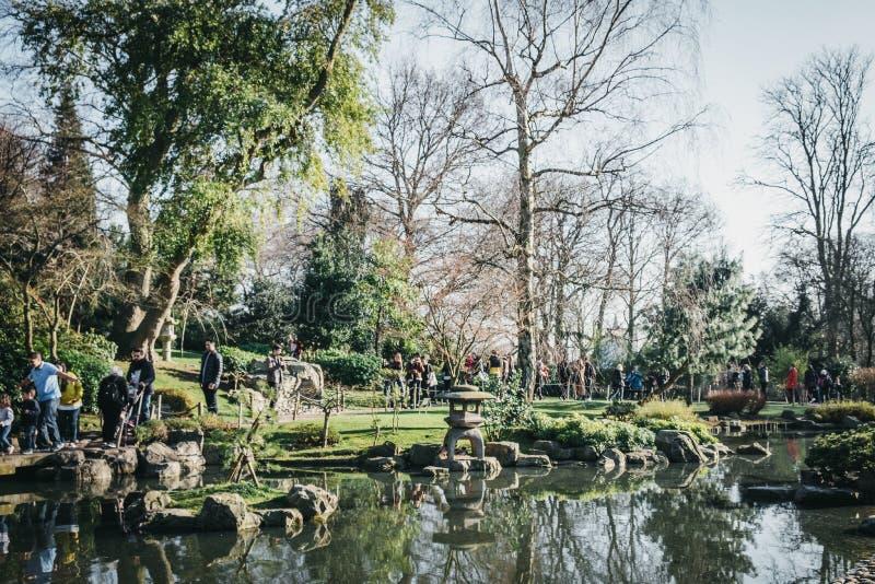 Люди идя внутри сада Киото в парке Голландии, Лондоне, Великобритании, на солнечный весенний день стоковая фотография