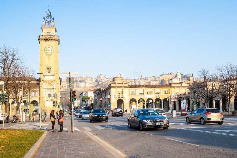 Люди и автомобили на улице Viale Roma в Бергаме стоковые изображения rf