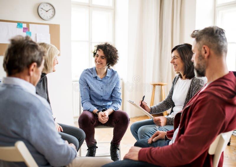 Люди и женщины сидя в круге во время терапии группы, говоря стоковые фото
