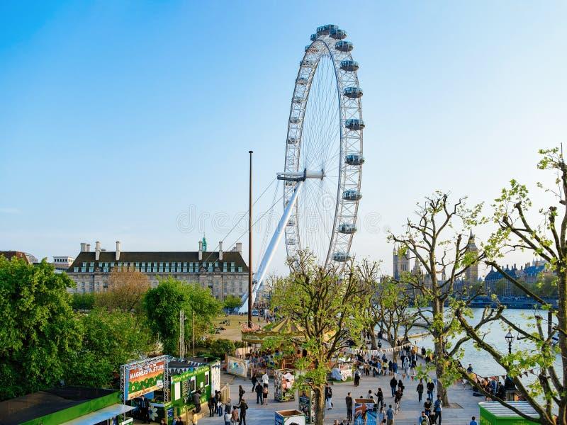 Люди на обваловке Виктория и колесе Ferris Лондоне глаза Лондона стоковые изображения