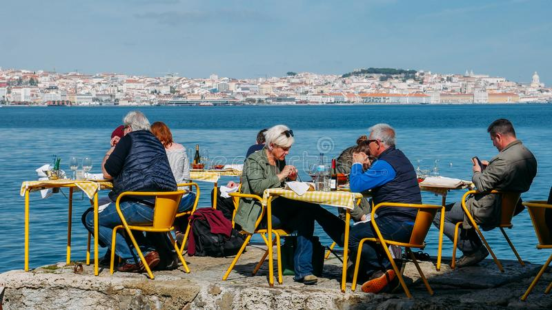Люди сидя на желтых таблицах ресторана в береге реки Тахо в городском пейзаже Cacilhas - Лиссабона в стоковое фото rf