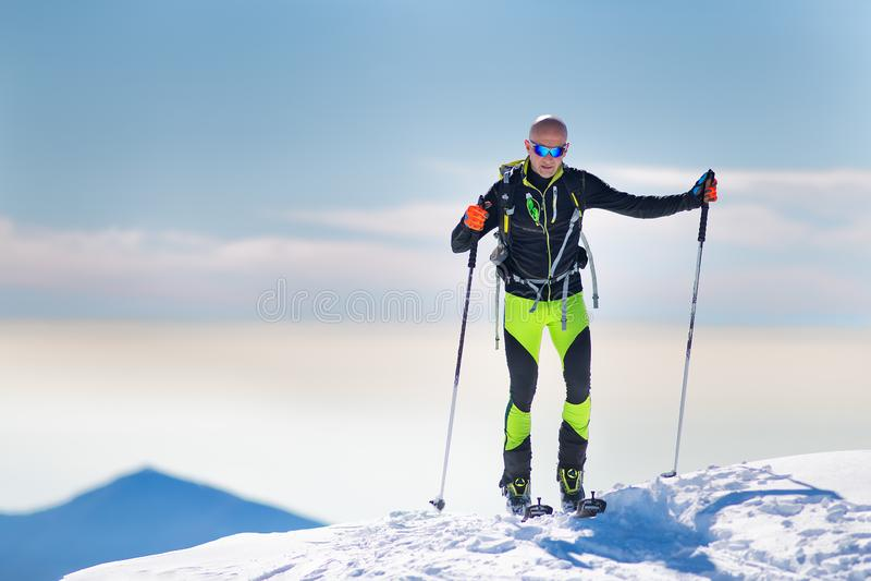 Лыжник альпиниста приезжая на саммит стоковое фото rf