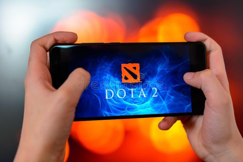 Лос-Анджелес, Калифорния, США - 9-ое марта 2019: Человек держит конец-вверх смартфона в его руках и играет dota 2 против стоковое изображение