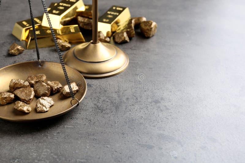 Лоток масштаба с шишками золота на серой таблице стоковые изображения rf