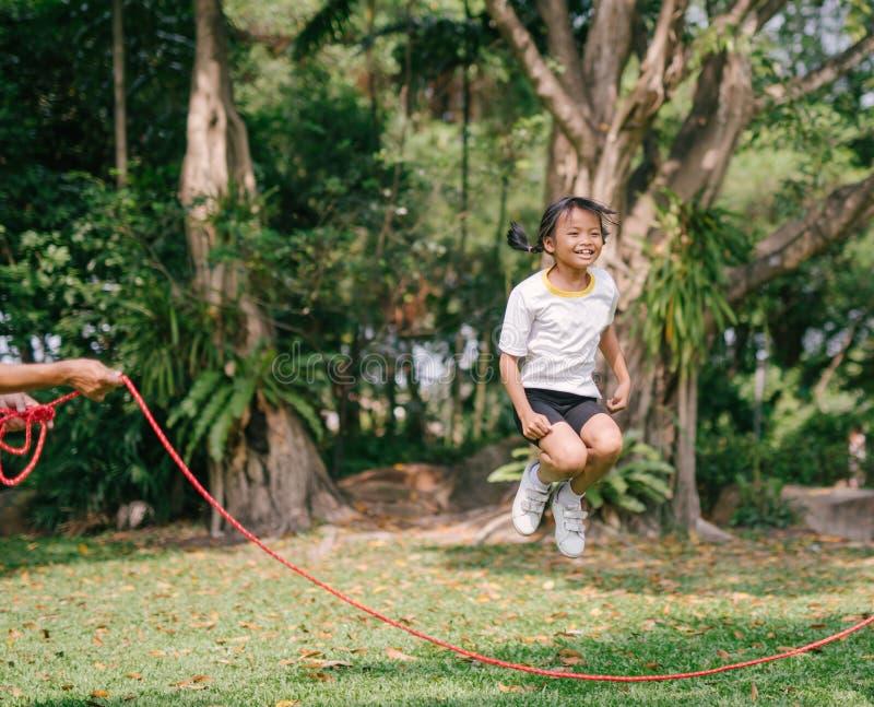 Маленькая азиатская девушка играя с прыгая веревочкой скача на зеленый природный парк стоковая фотография rf