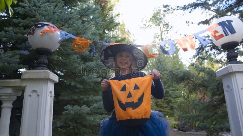 Маленькая ведьма держит фокус или сумка обслуживания, просит помадки outdoors, партия хеллоуина стоковые изображения