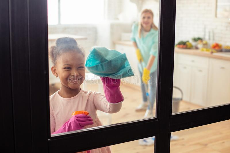Маленькая милая девушка усмехаясь пока помогающ ее матери с чисткой стоковые фотографии rf