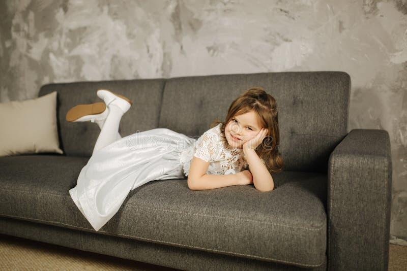 Маленькая девочка в белом платье на софе Пятилетняя девушка дома стоковое фото rf
