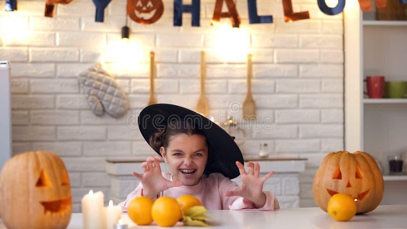 Маленькая девочка в страшном костюме ведьмы пробуя вспугнуть детей, партии хеллоуина стоковые изображения rf