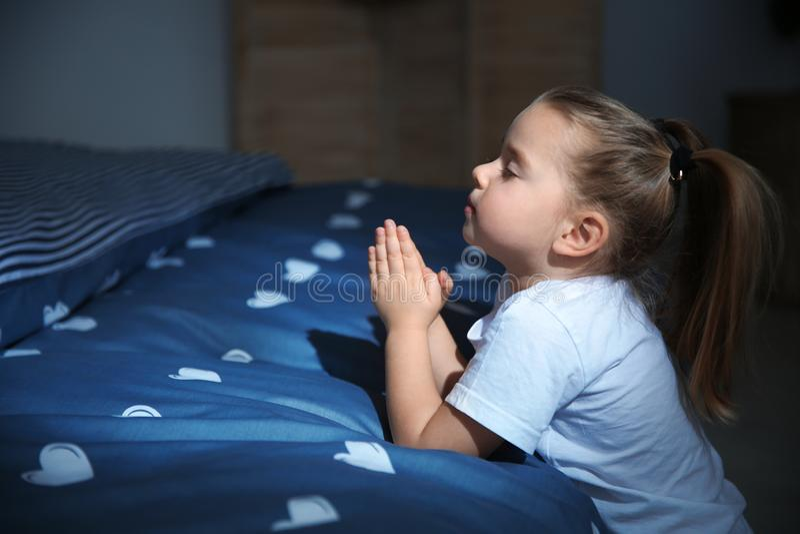 Маленькая девочка говоря молитву времени ложиться спать около кровати в комнате стоковое изображение rf