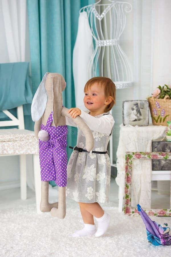 Маленькая девочка играя с куклой и усмехаться стоковое фото