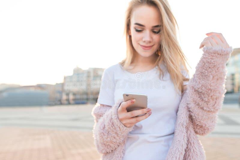 Маленькая девочка нося розовое пальто использует смартфон на улицах города на заходе солнца стоковое изображение rf
