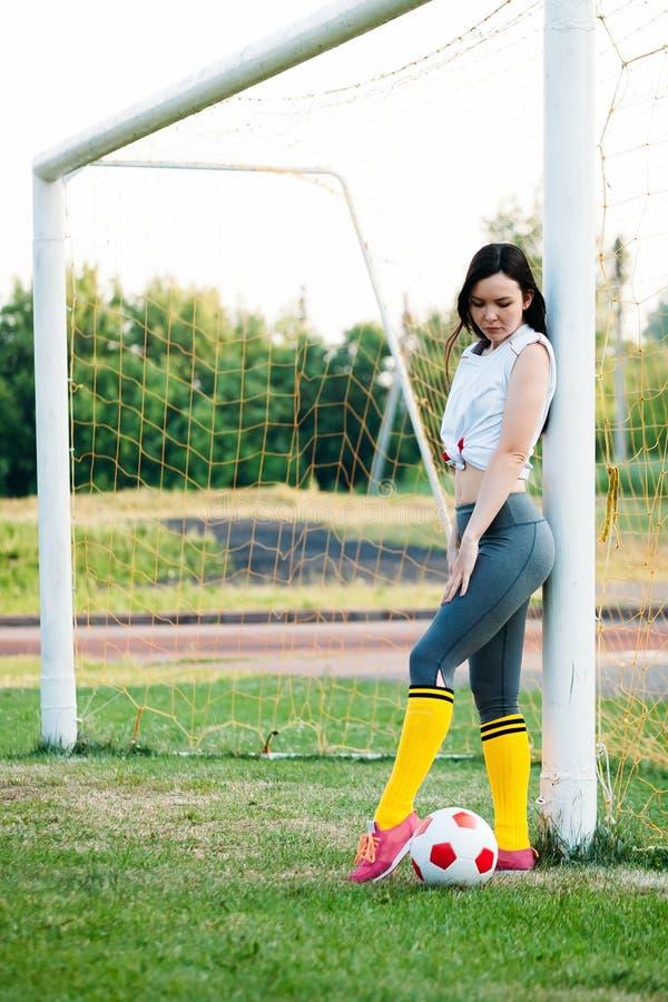 Маленькая девочка представляя с футбольным мячом на цели футбола стоковые фото