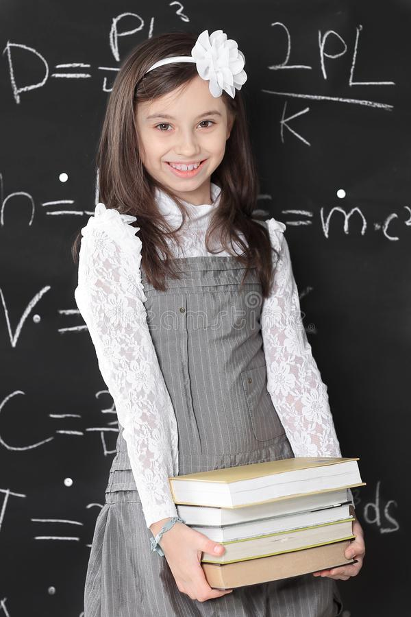 Маленькая девочка держит стог книг стоя около школьного правления стоковые фотографии rf