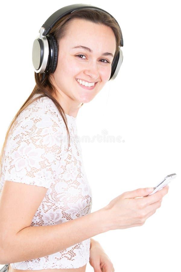 Маленькая девочка слушая музыку с наушниками наслаждаясь музыкой стоковое фото