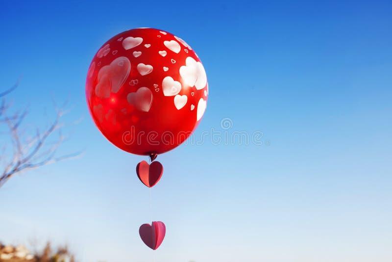 Маленькая девочка с красным воздушным шаром на голубом небе стоковое изображение rf