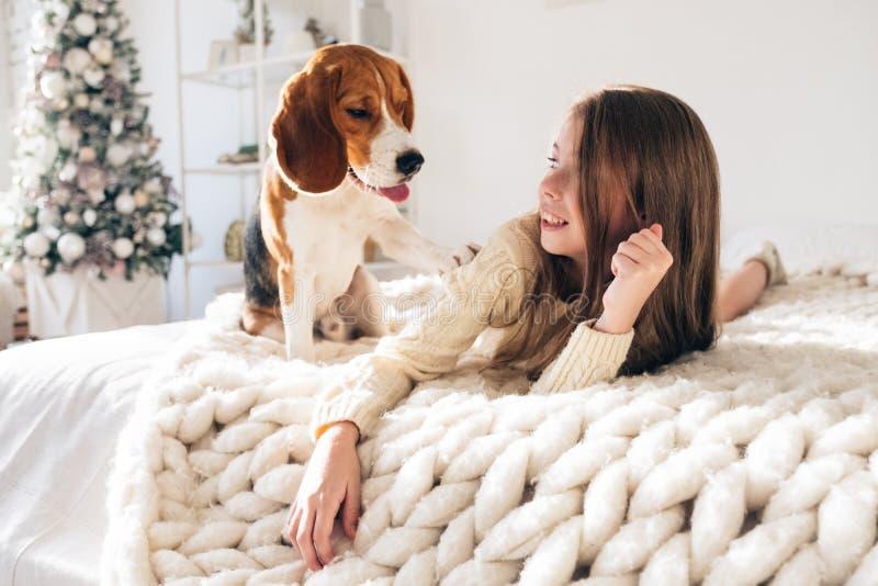 Маленькая девочка с собакой лежа на кровати и смеяться стоковое изображение rf