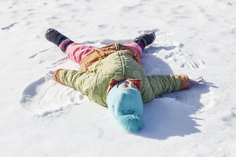 маленькая девочка рисует на ангеле снега поле глубины отмелое стоковое изображение rf