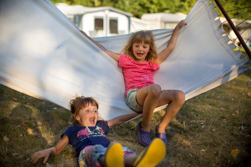 Маленькие девочки имея потеху на гамаке стоковые фото