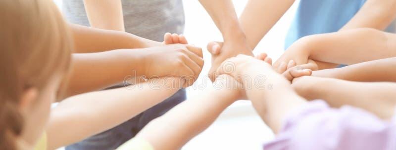 Маленькие дети держа их руки совместно на светлой предпосылке стоковые фото