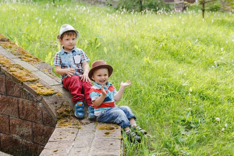 Маленький жизнерадостный младенец 2 в шляпах на зеленой траве летом стоковое изображение rf