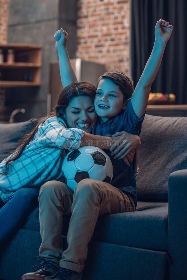 Маленький сын и его красивая мать обнимая и веселя пока наблюдающ футбольный матч на кресле стоковые фотографии rf