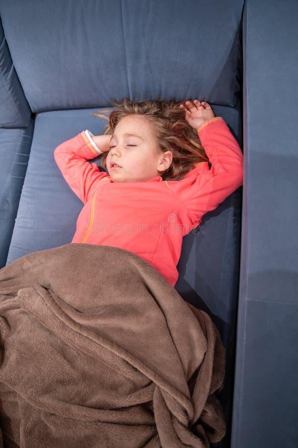 Маленький ребенок лежа на софе спать с оружиями вверх стоковое изображение rf