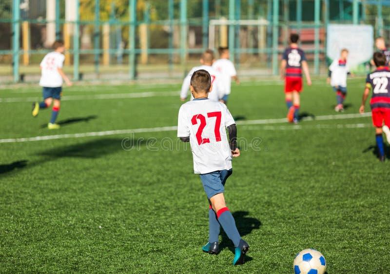 Мальчики в красном белом sportswear бежать на футбольном поле Молодые футболисты капают и пинают шарик футбола в игре тренировка стоковые фото
