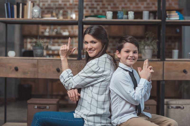 Мальчик и его красивая мать представляя и делая жест если держащ стоковые фото