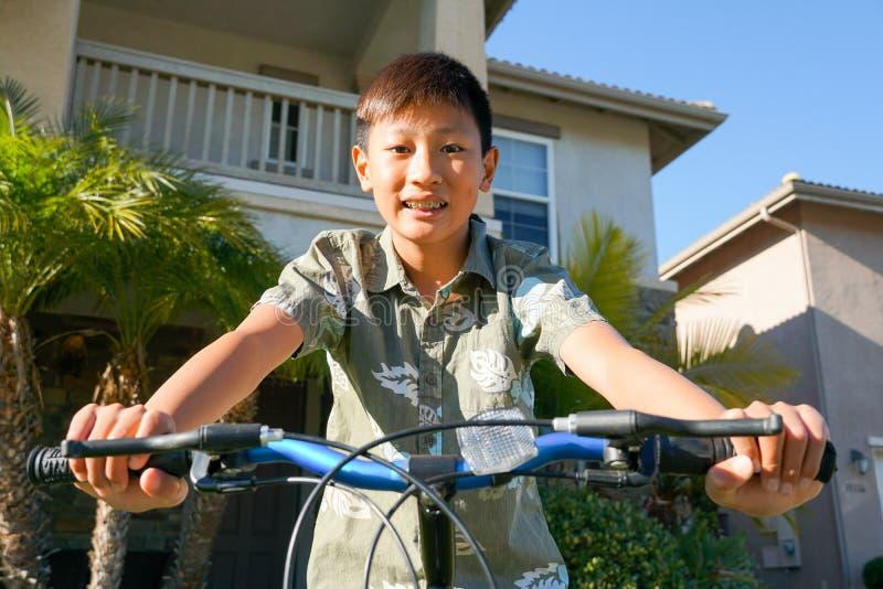 Мальчик молодого парня азиатский с расчалками на его велосипеде перед домом стоковые фото