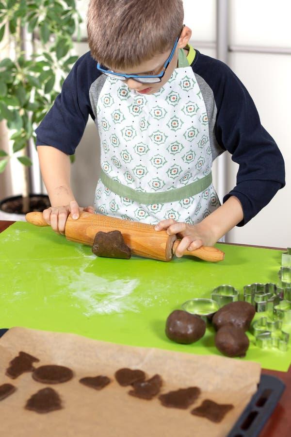 Мальчик нося рисберму кухни свертывая коричневое тесто с деревянной вращающей осью на доске печенья зеленого цвета силикона Ребен стоковые фото