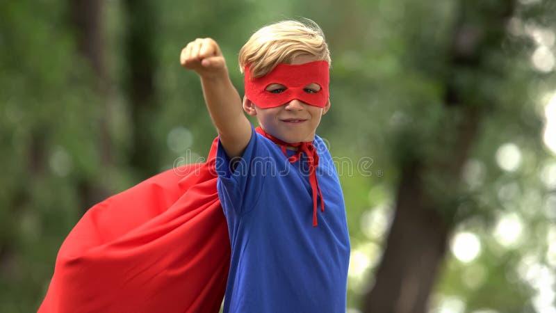 Мальчик супергероя играя в парке, претендуя лететь, храбром ребенке и концепции победителя стоковая фотография rf