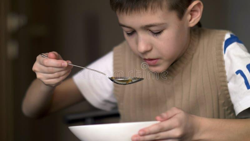Мальчик с аппетитом ест суп, имеет потеху стоковые фотографии rf